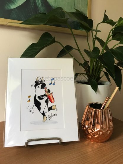 Cow playing Sax Print in mat displayed on a desk